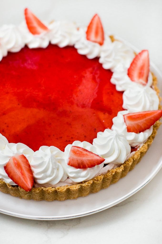 Easy and simple to make white chocolate mousse tart topped with strawberry jam glaze. No baking involved!